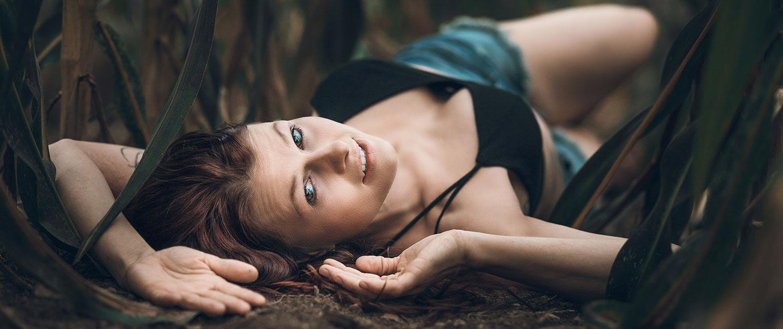 Frau mit braunen Augen liegend im Maisfeld mit sommerlichen Outfit
