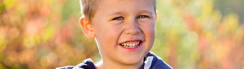 lachender Junge mit blonden Haaren im Herbst