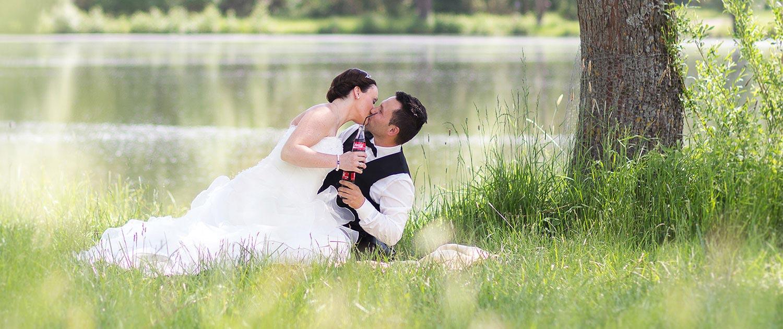 Braut und Bräutigam am See und sich dabei küssen