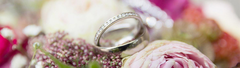 Detailaufnahme von den Trauringen auf dem Brautstrauß von einer Hochzeit