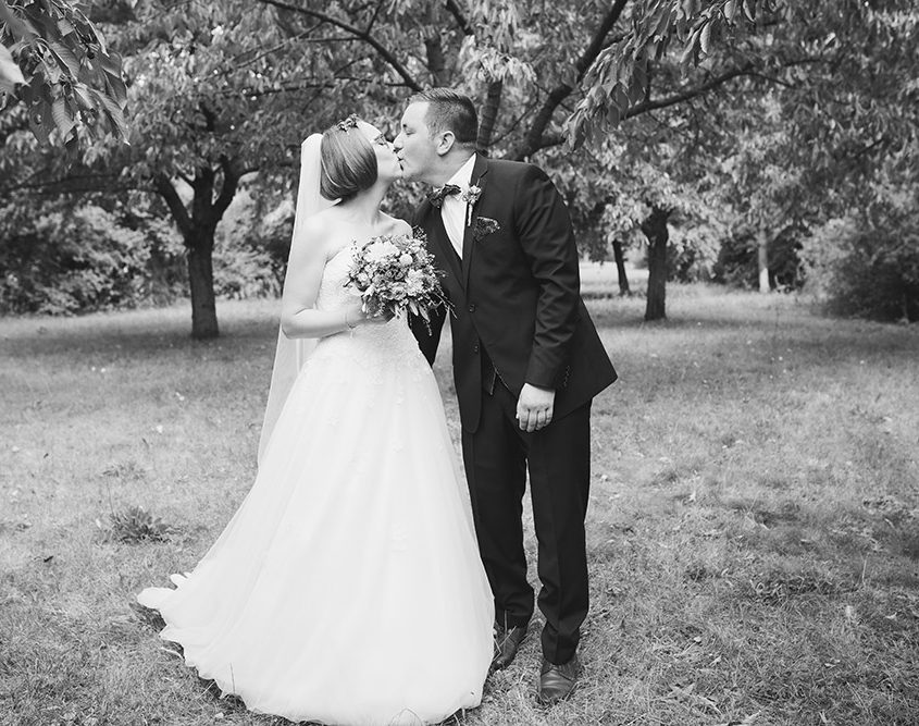 Brautpaar küsst sich beim Brautpaarshooting zwischen Obstbäumen