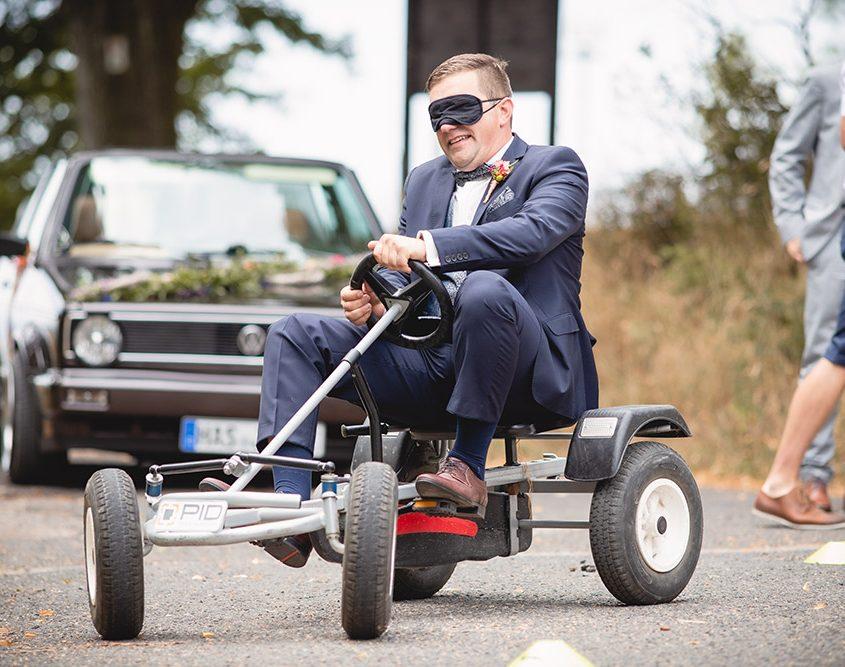 Bräutigam fährt blind Kettcar Slalom nach der kirchlichen Trauung in Zeil am Main
