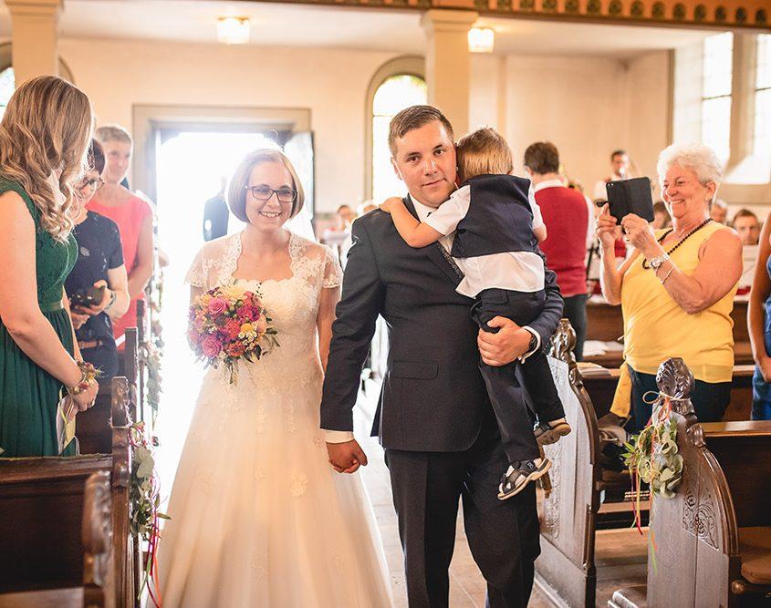 Brautpaar beim Einlaufen in die Kirche mit Sohn auf dem Arm