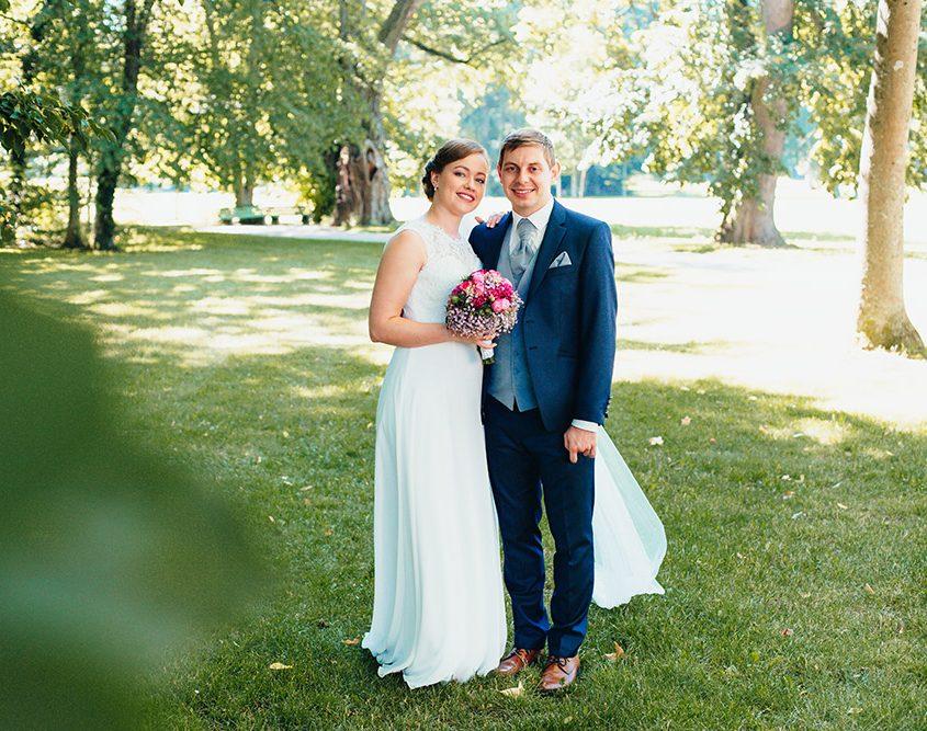 Braut lehnt im Schlosspark an ihren künftigen Mann