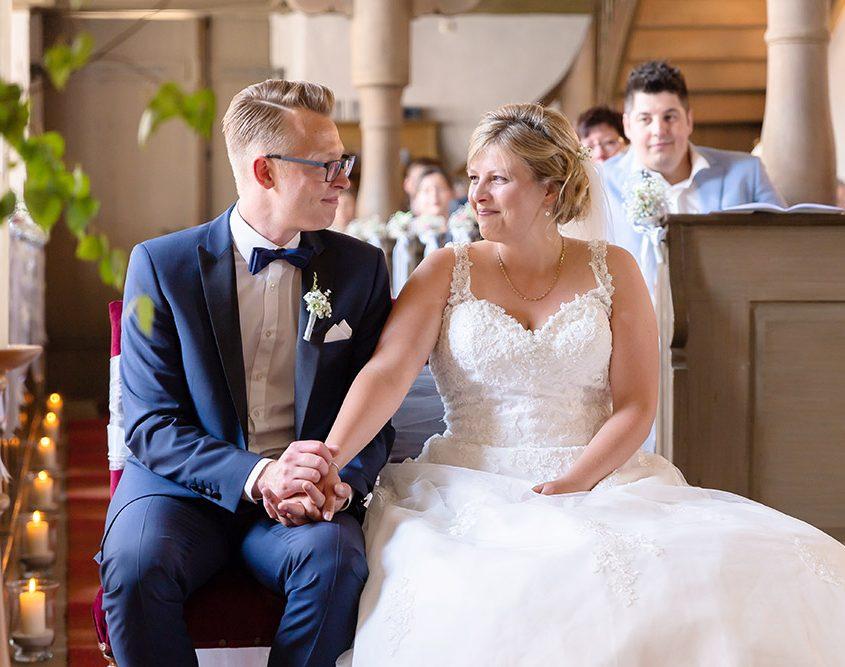 glückliches Brautpaar schaut sich in der Kirche in die Augen