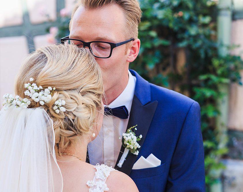 Bräutigam küsst seine Braut liebevoll auf die Stirn