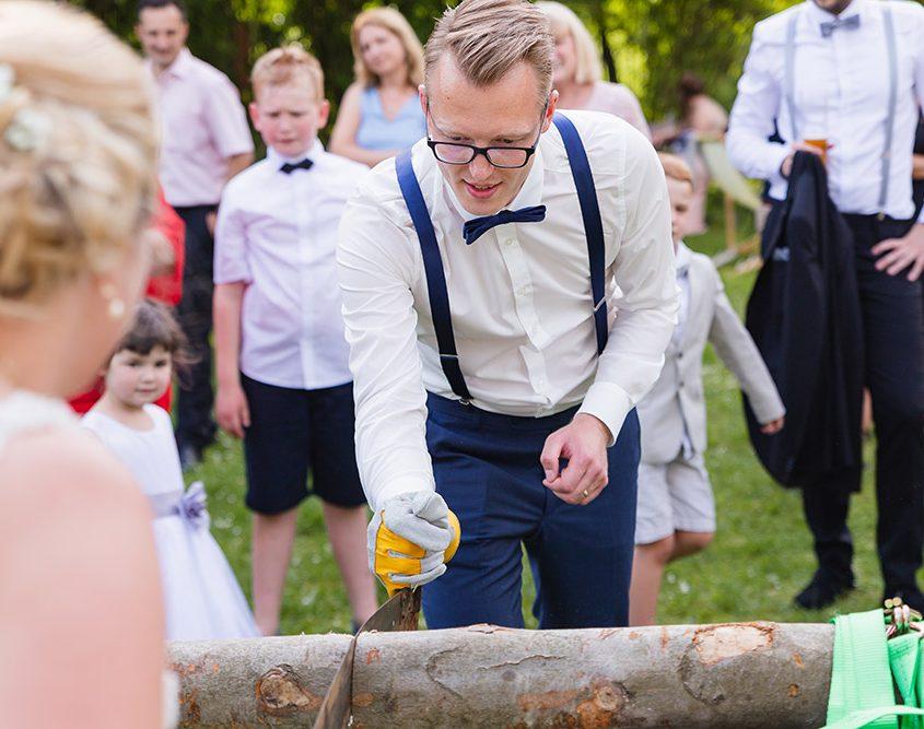 Braut und Bräutigam müssen einen Baumstamm druchsägen