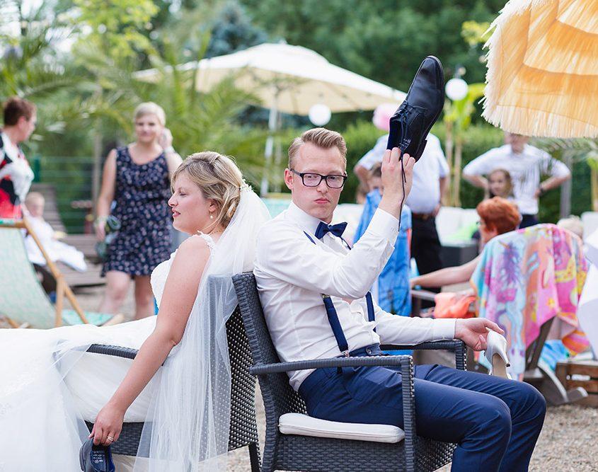 Brautpaar bei einen lustigen Spiel mit ihren Schuhen auf der Feier