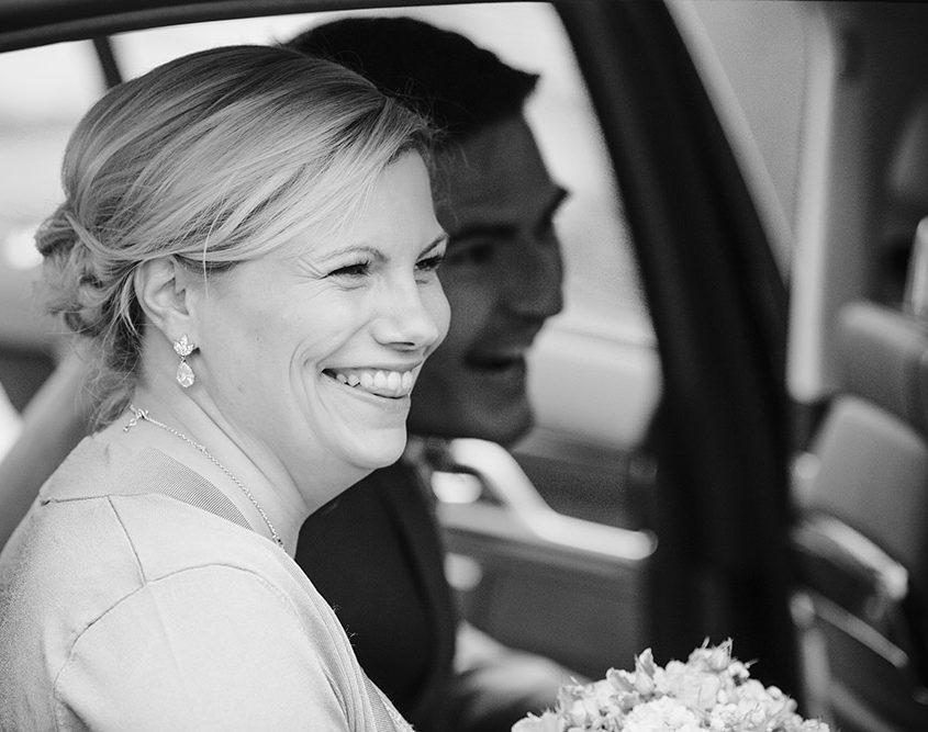 Lachendes Brautpaar sitzt mit einen lachen im Brautauto