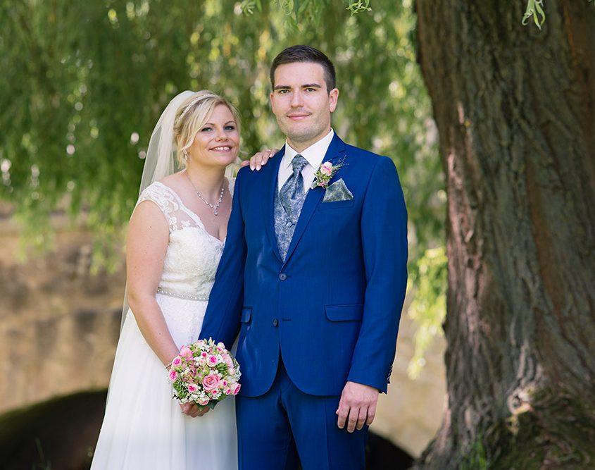 Glückliches Brautpaar steht im Schlosspark unter einer Weide