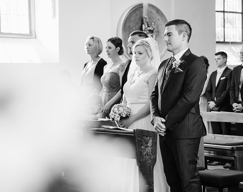Brautspaar steht andächtig in der Kirche vorm Altar
