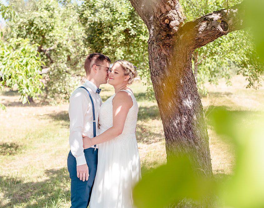 Braut und Bräutigam liegen sich beim Fotoshooting in den Armen
