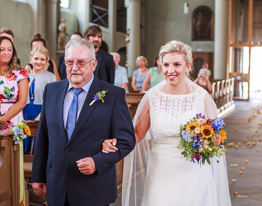 Braut wird von ihren Vater in die Kirche zum Altar geleitet