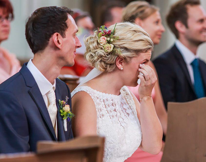Braut sitzt neben ihren Mann in der Kirche und weint vor Glück
