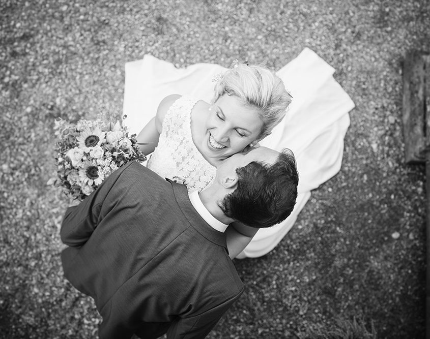 Bräutigam küsst seine lachende Braut am Hals in monochrom