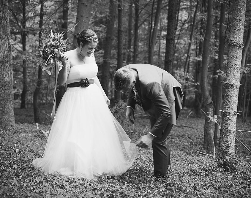 Der Bräutigam befreit das Hochzeitskleid von Ästen beim Brautpaarshooting im Wald